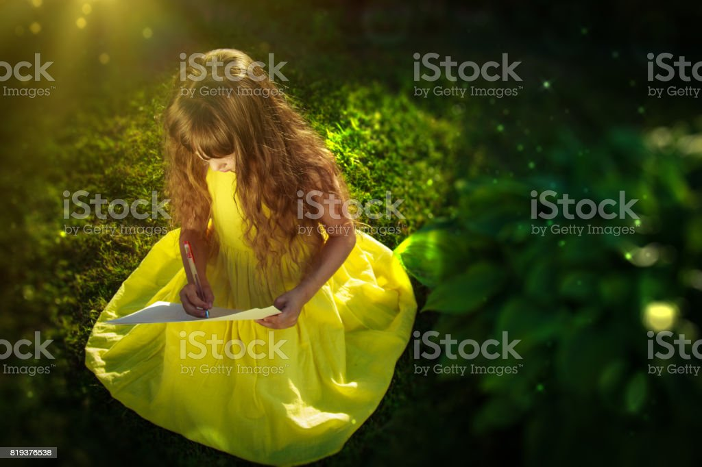 A girl in a yellow dress sits on the grass and draws stock photo