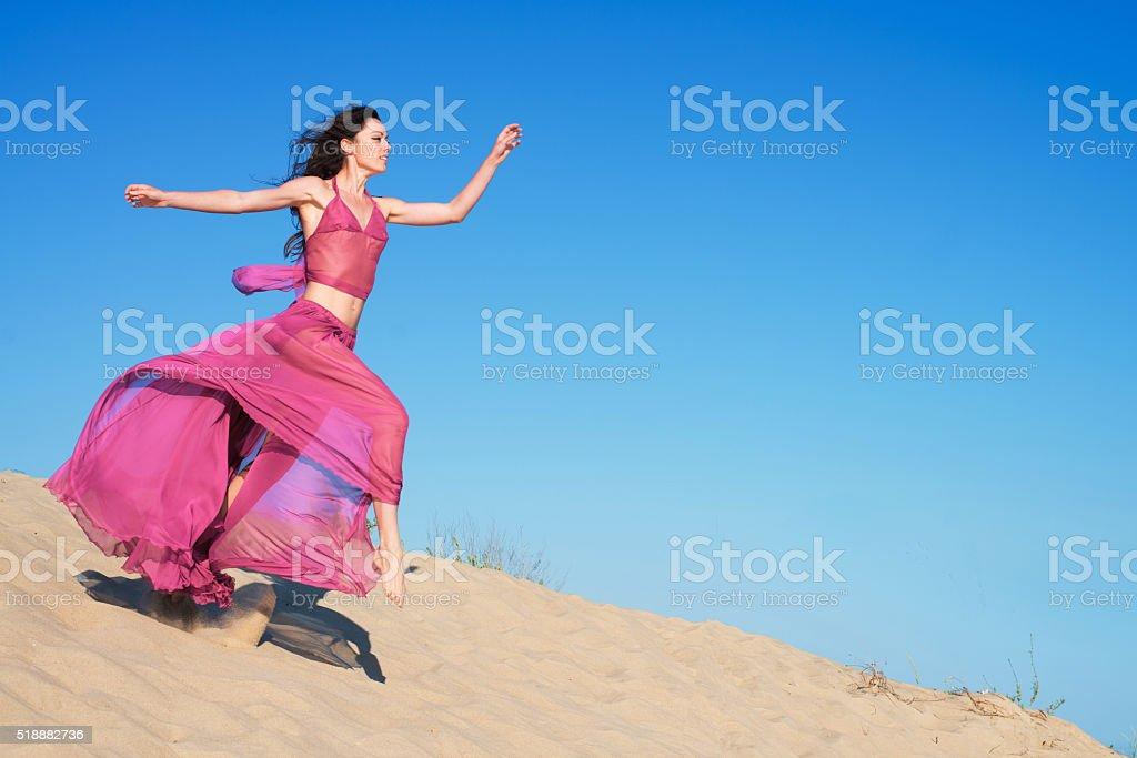 Girl in airy dress running on sand dunes stock photo