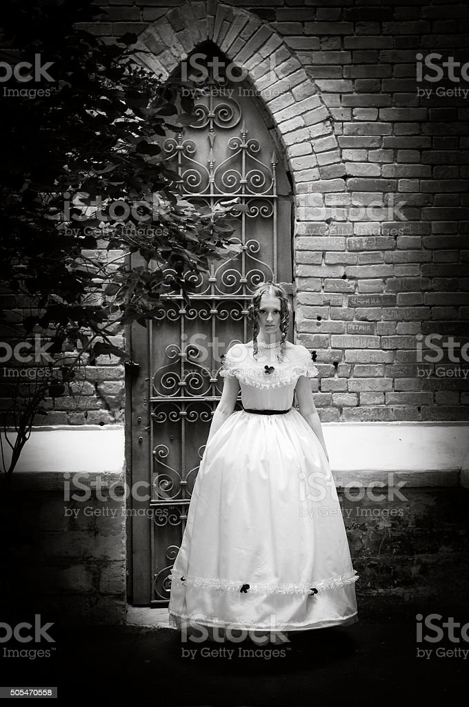 Girl in ancient dress standing on a background Gothic arches stock photo