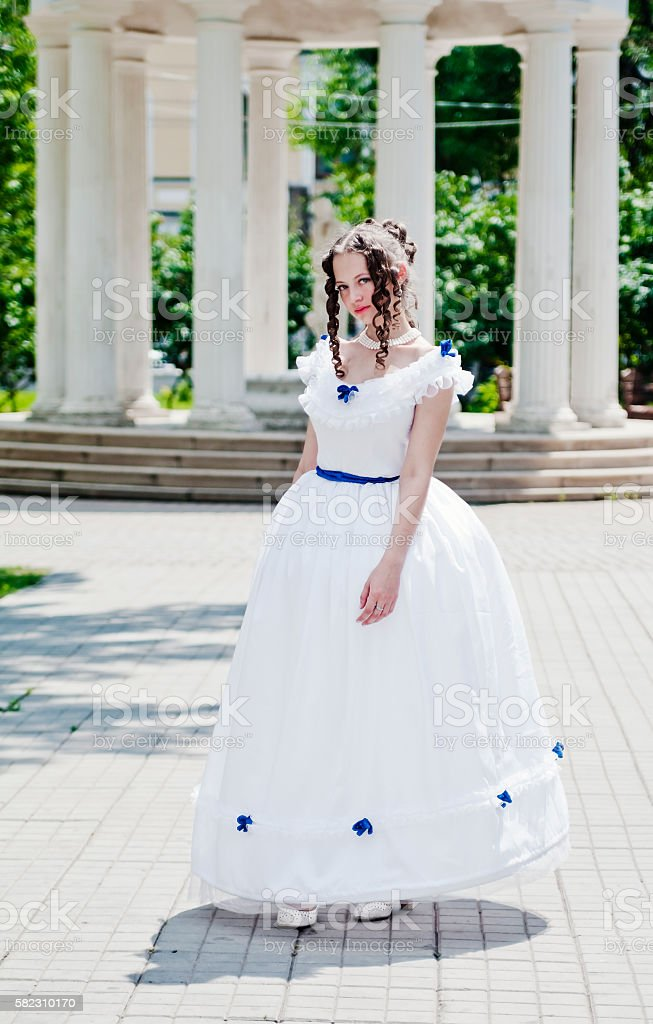 Girl in ancient dress with crinoline on background of rotunda stock photo
