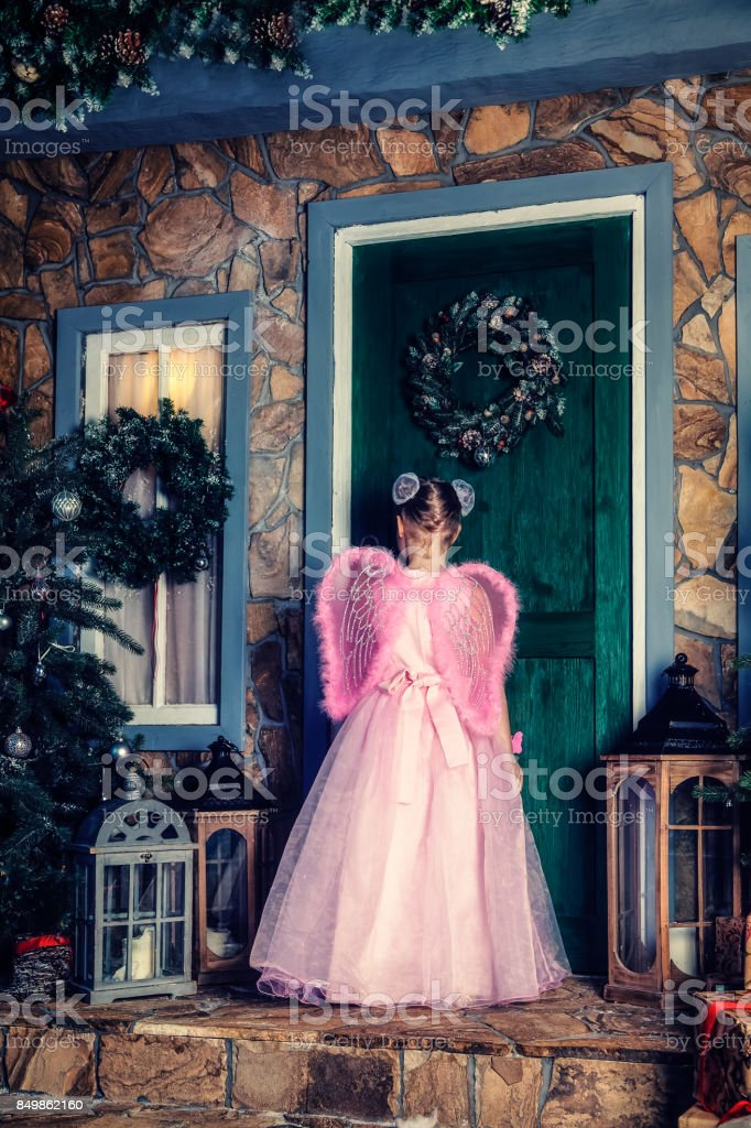 Girl in angel costume is knocking at the door stock photo