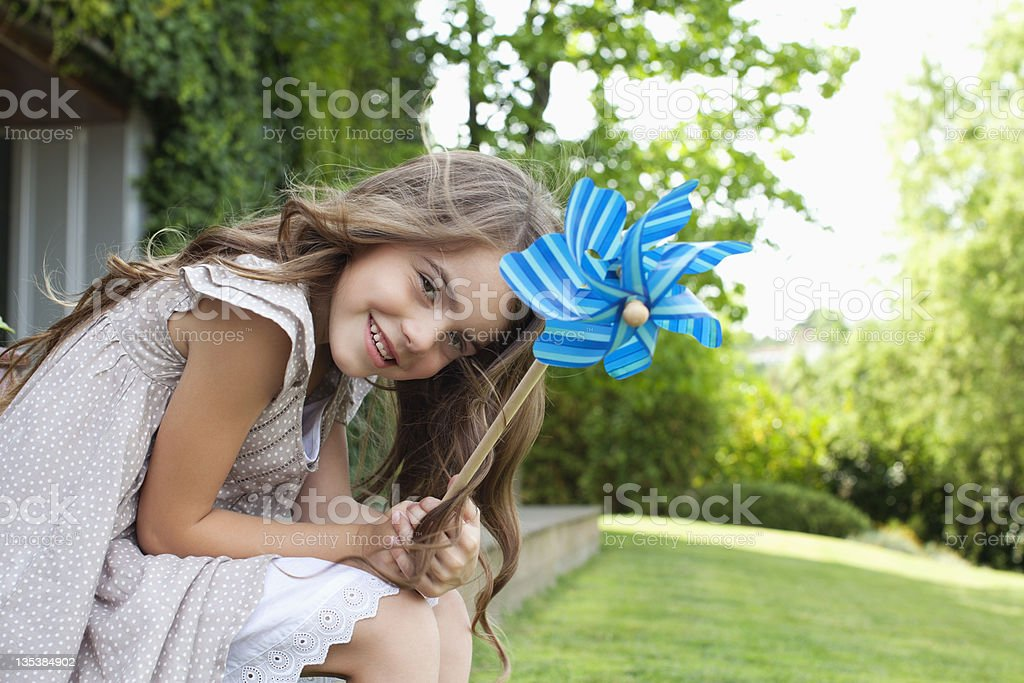 Girl in backyard holding pinwheel stock photo
