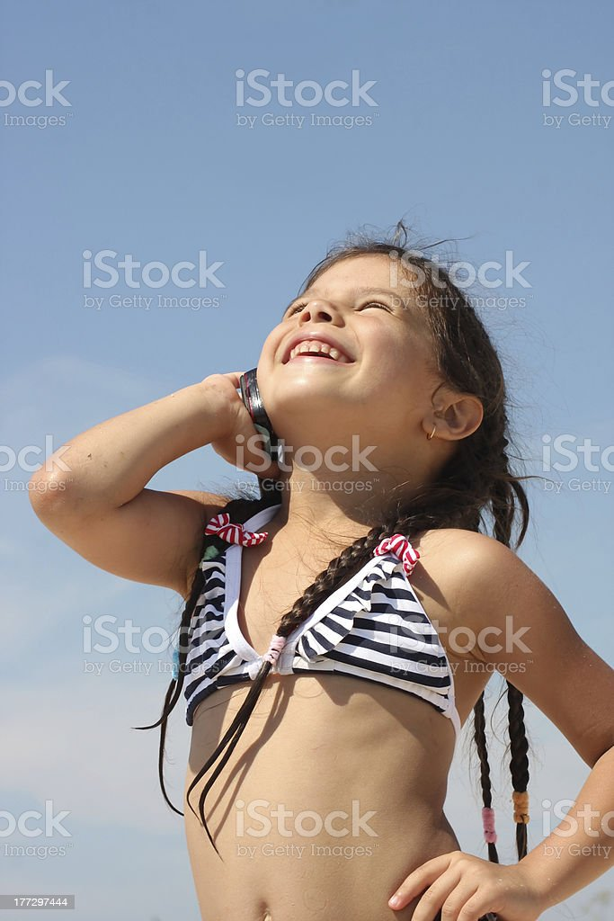 Girl in bathing suit talking on cell phone stock photo