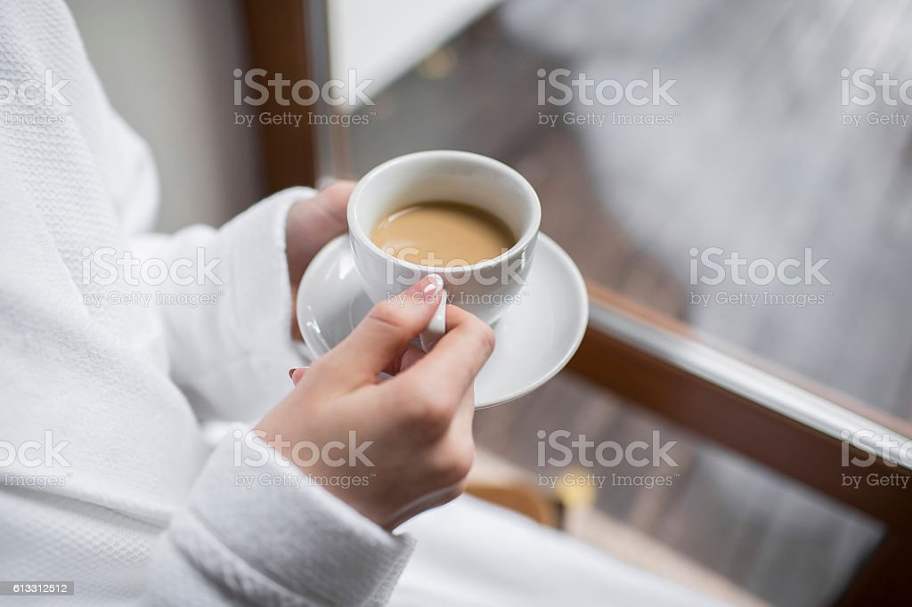 girl in Bathrobe at the window with Cup of coffee stock photo