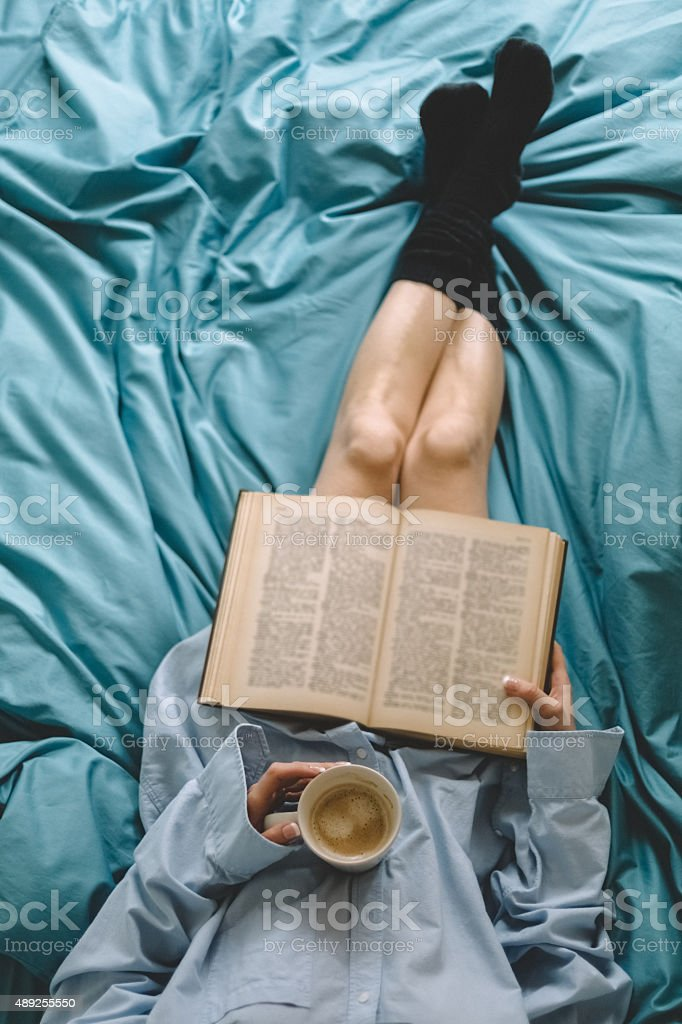 Girl in bed reading a book stock photo