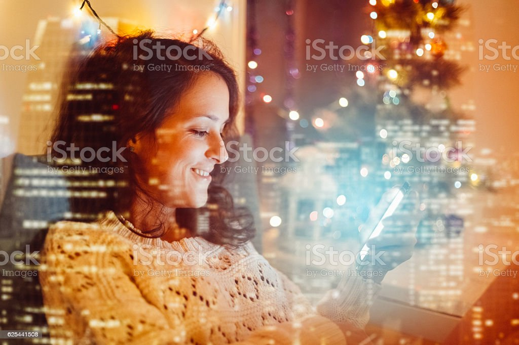 Girl in bed texting on phone stock photo