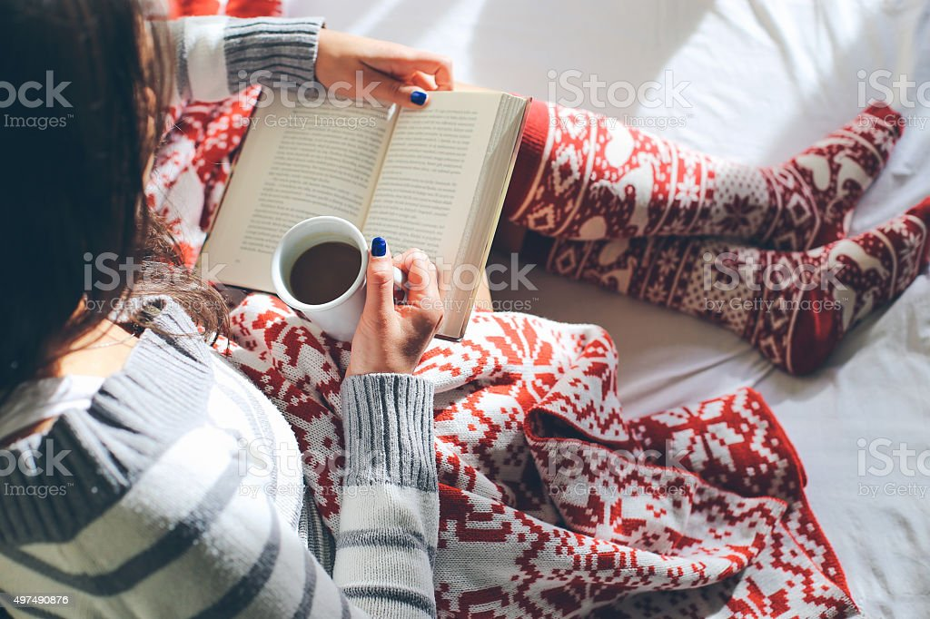 Girl in bed with coffee cup reading a book stock photo