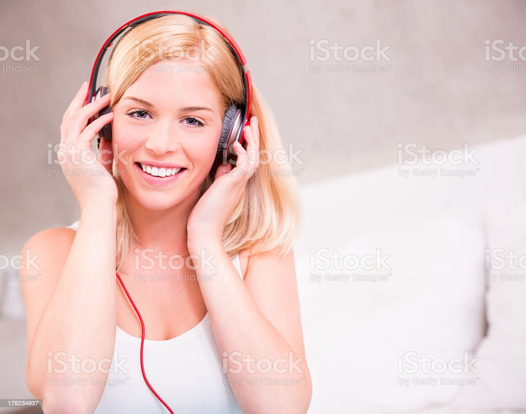 Girl in bed with headphones listening to music royalty-free stock photo