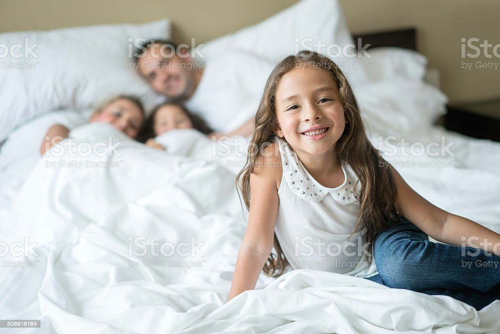 Girl in bed with her family stock photo
