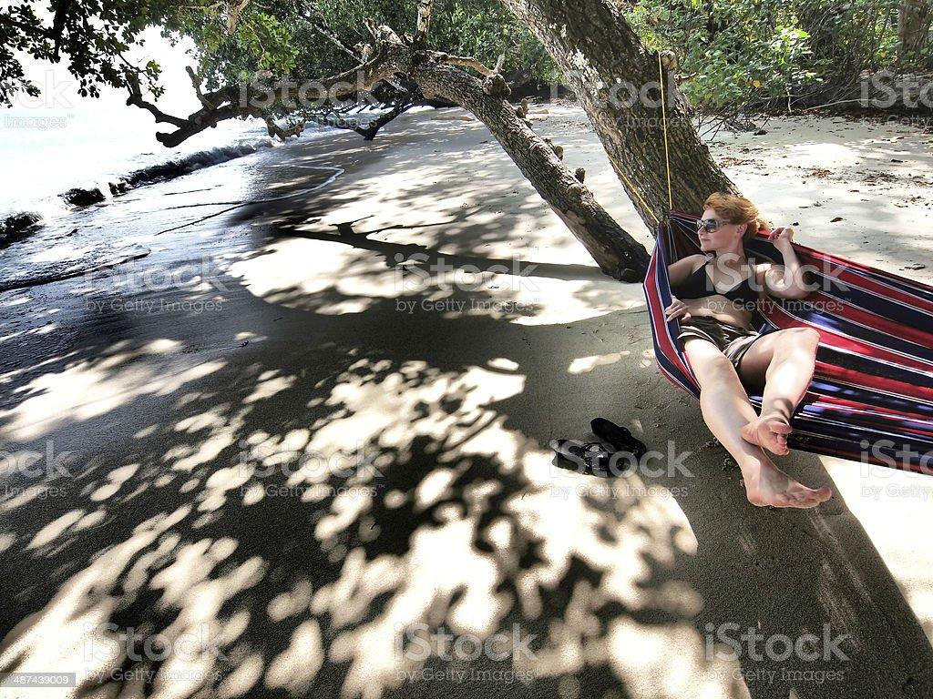 Girl in bikini laying in hammock on beach by ocean. stock photo