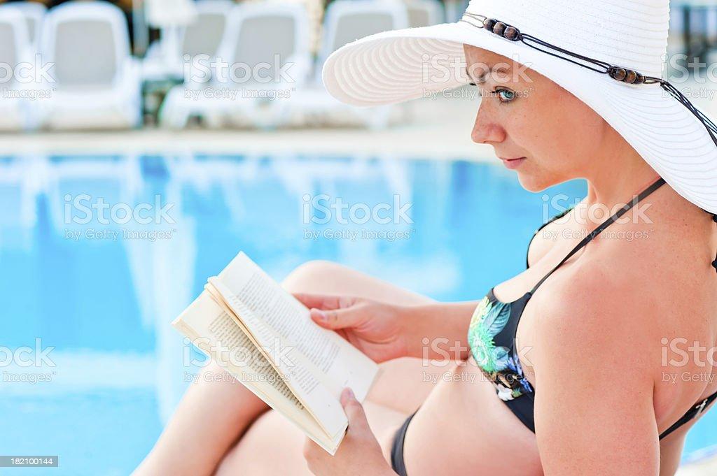 girl in bikini reading a book near the pool royalty-free stock photo