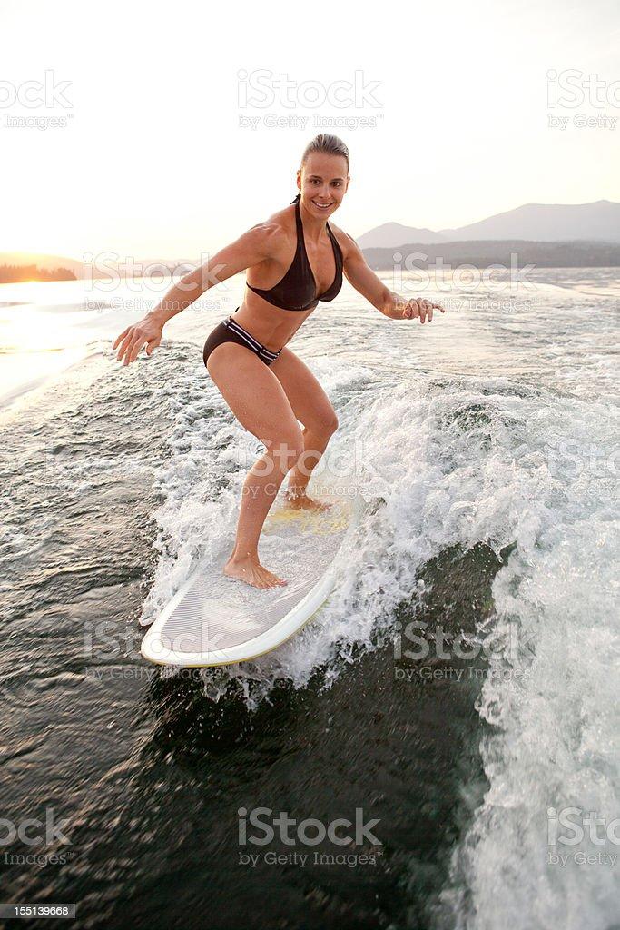 Girl in bikini wake surfing stock photo