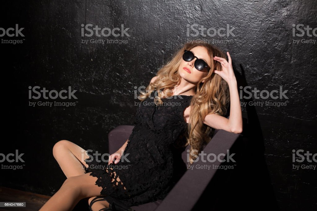 girl in black dress glasses and sitting stock photo
