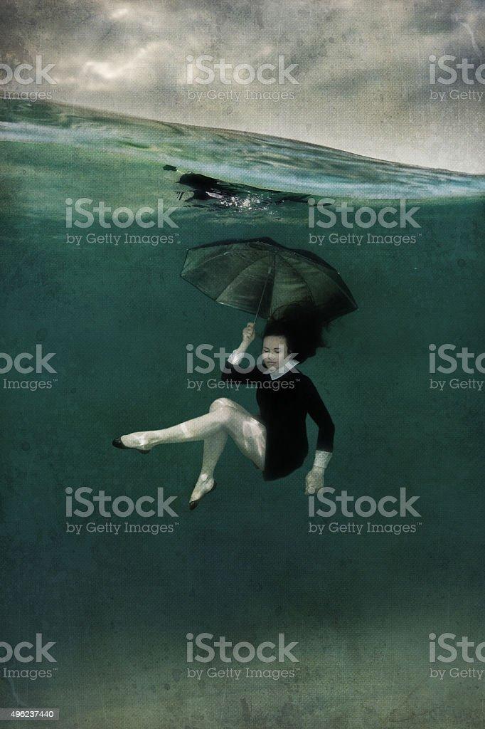 Girl in black dress underwater stock photo