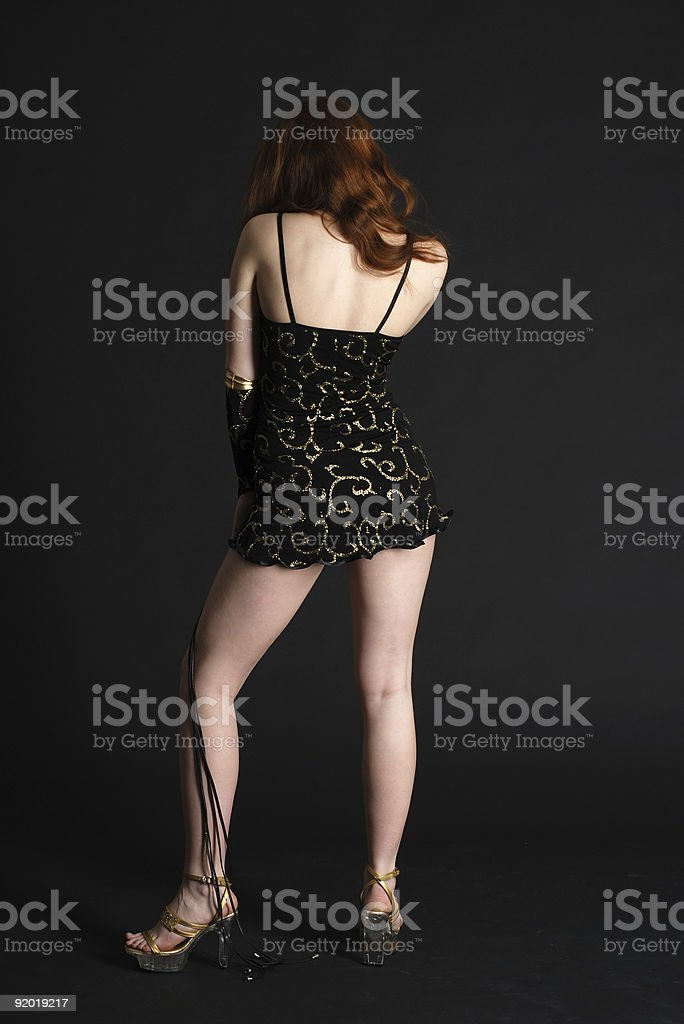 Girl in black short dress stands back royalty-free stock photo