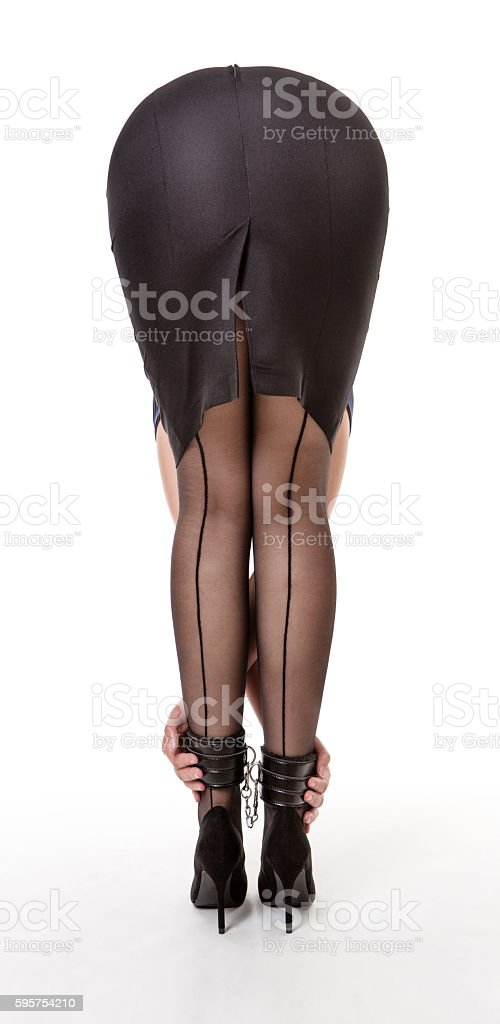 Girl in black skirt bends forward stock photo