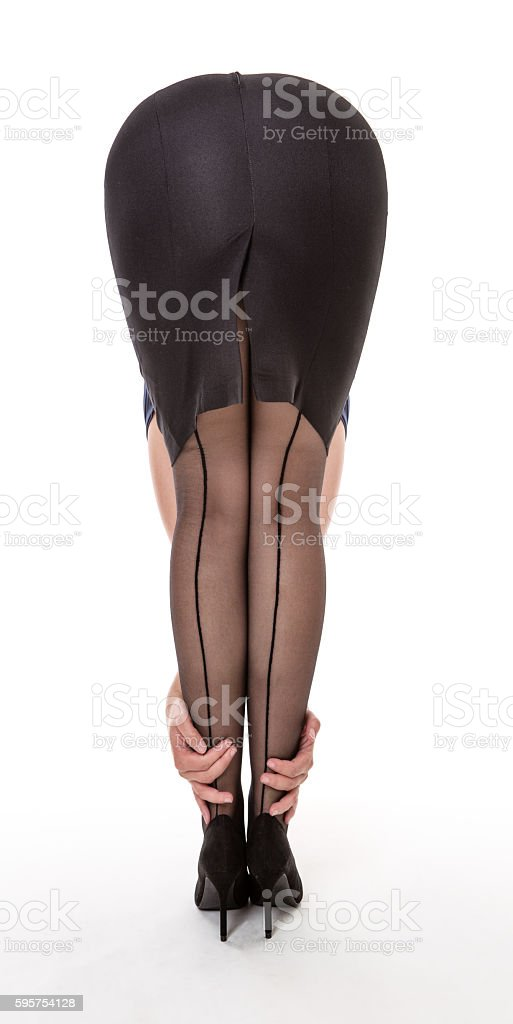 Girl in black suit bends forward stock photo