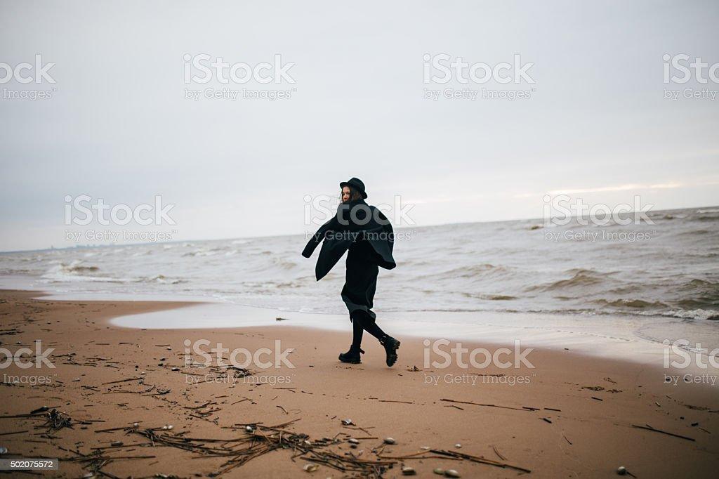 girl in black caminando en el mar foto de stock libre de derechos