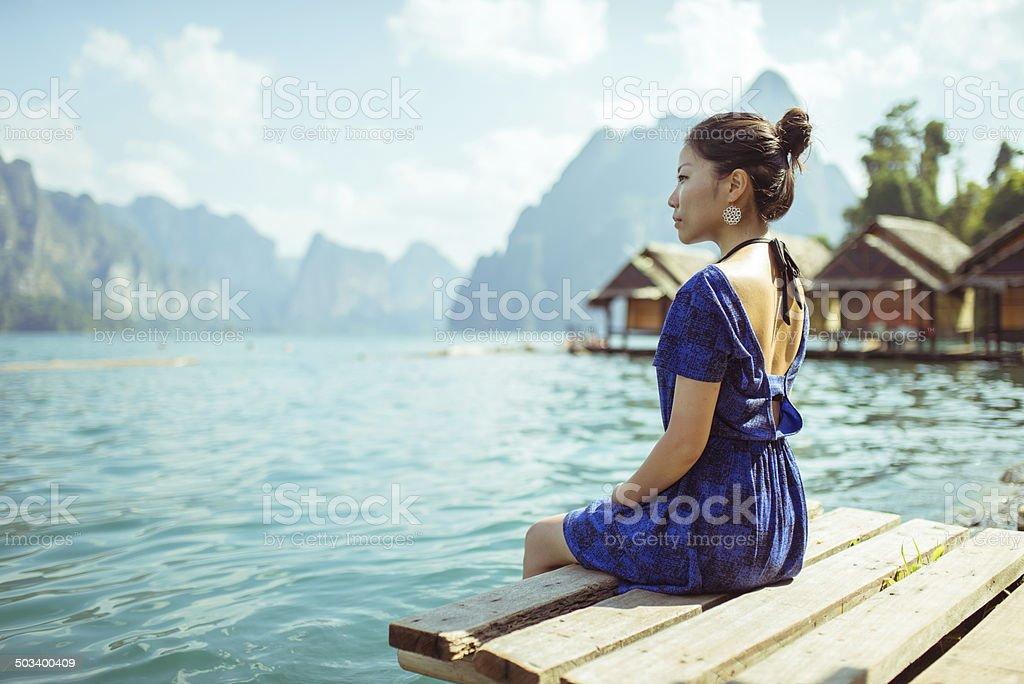 Mädchen im blauen Kleid sitzt am See Lizenzfreies stock-foto