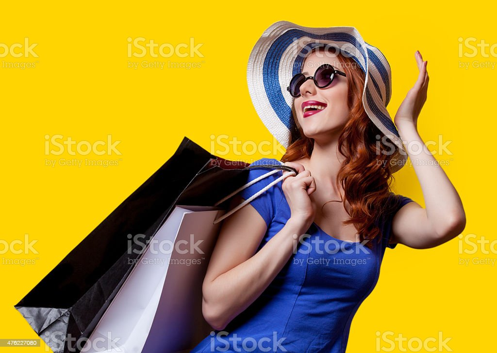 girl in blue dress with shopping bags stock photo