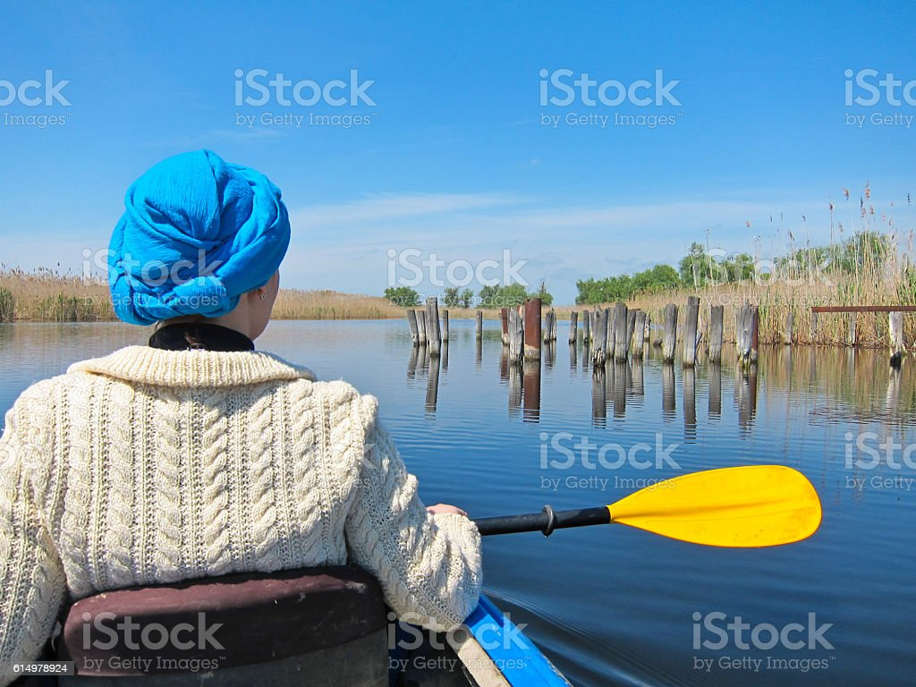 Girl in blue turban and yellow paddle in a kayak stock photo