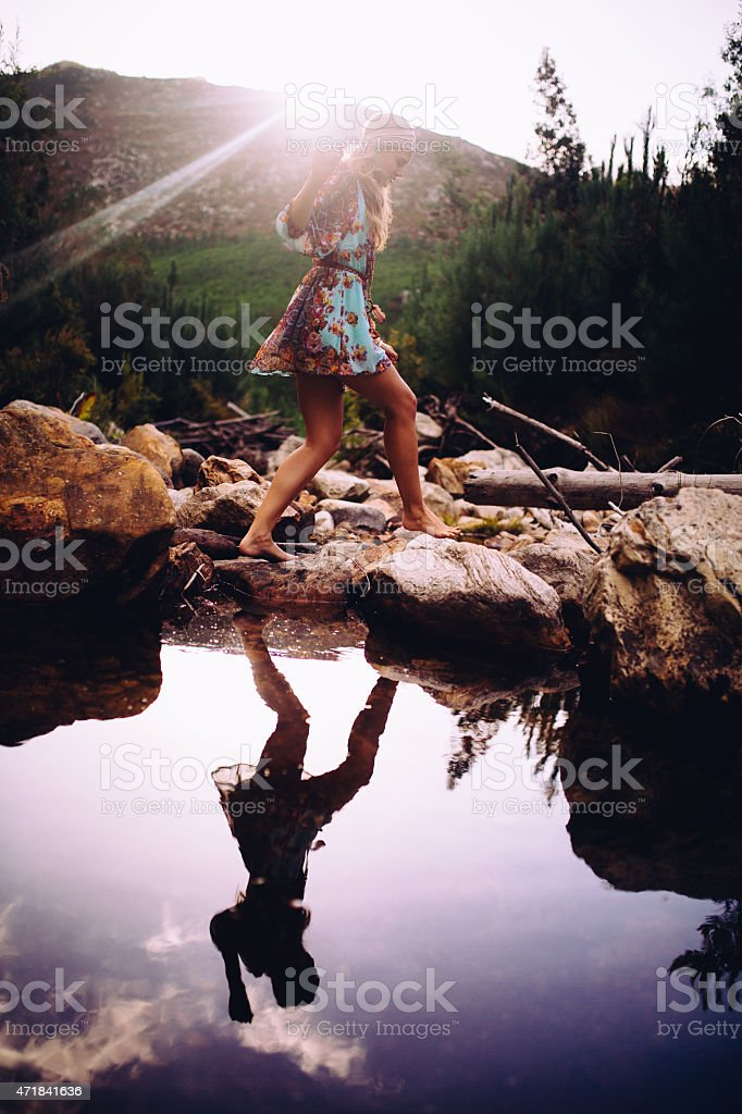 Girl in boho floral dress stepping over stones at lake stock photo