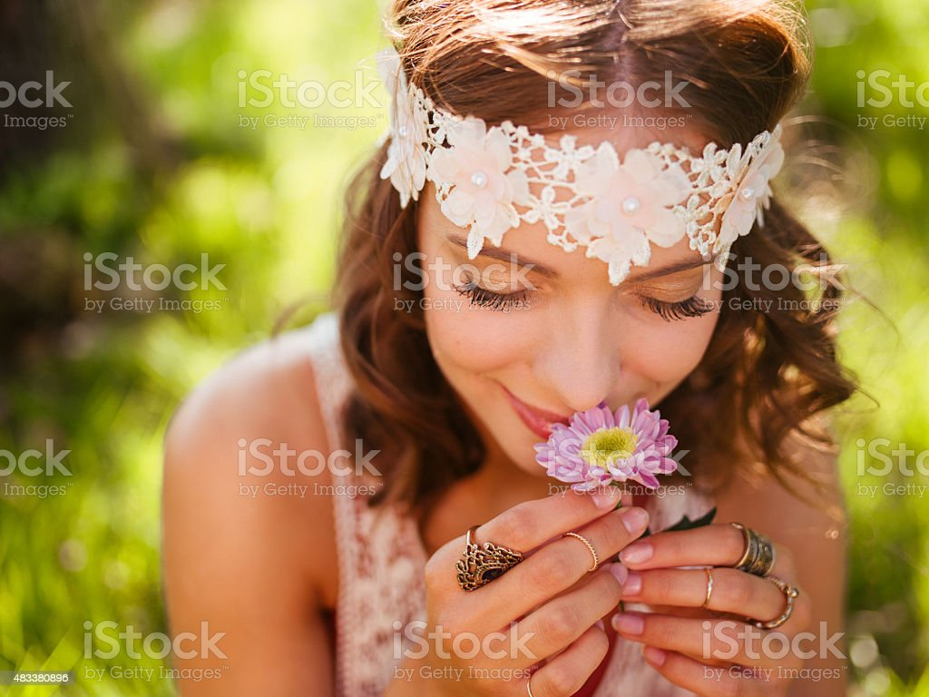 Girl in boho style smelling a fresh flower in nature stock photo
