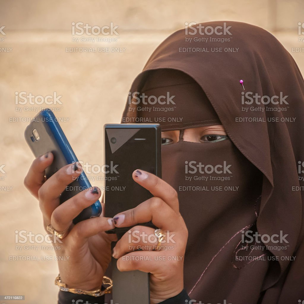 Girl in brown burqua with phones stock photo