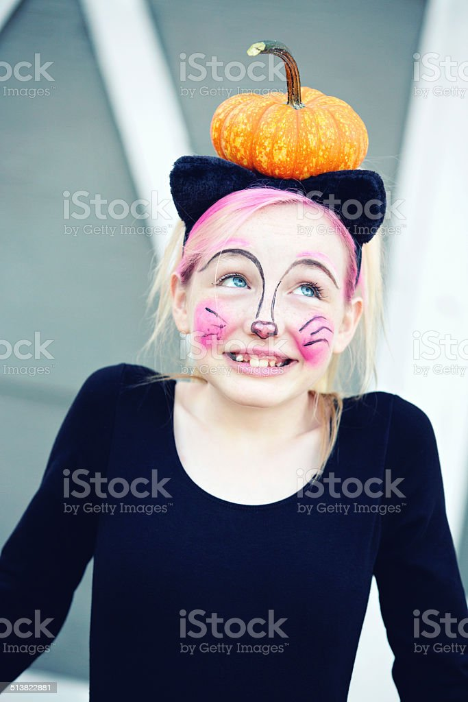 Girl In Cat Costume Balancing Pumpkin On Head stock photo