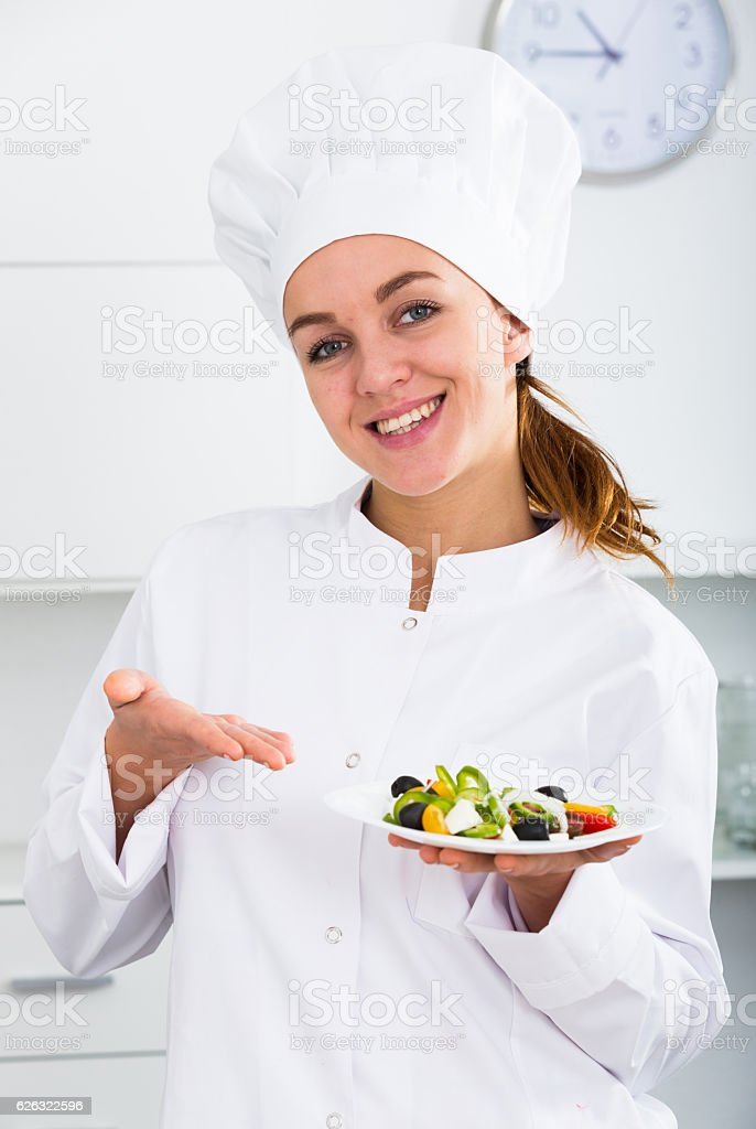 girl in chef's hat and white coat showing salad stock photo