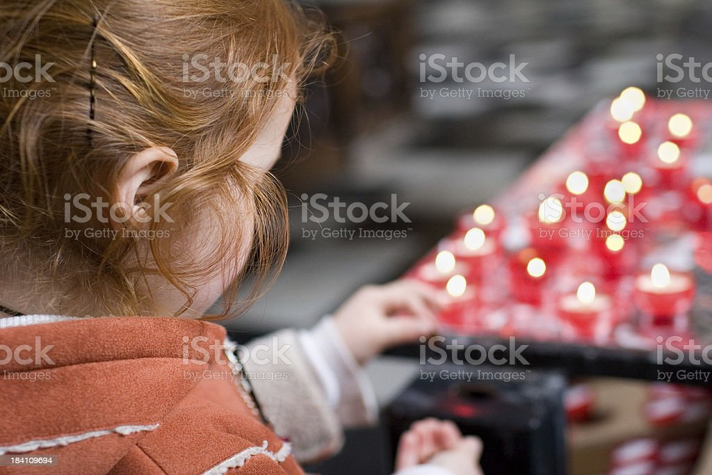 girl in church, lighting candles royalty-free stock photo