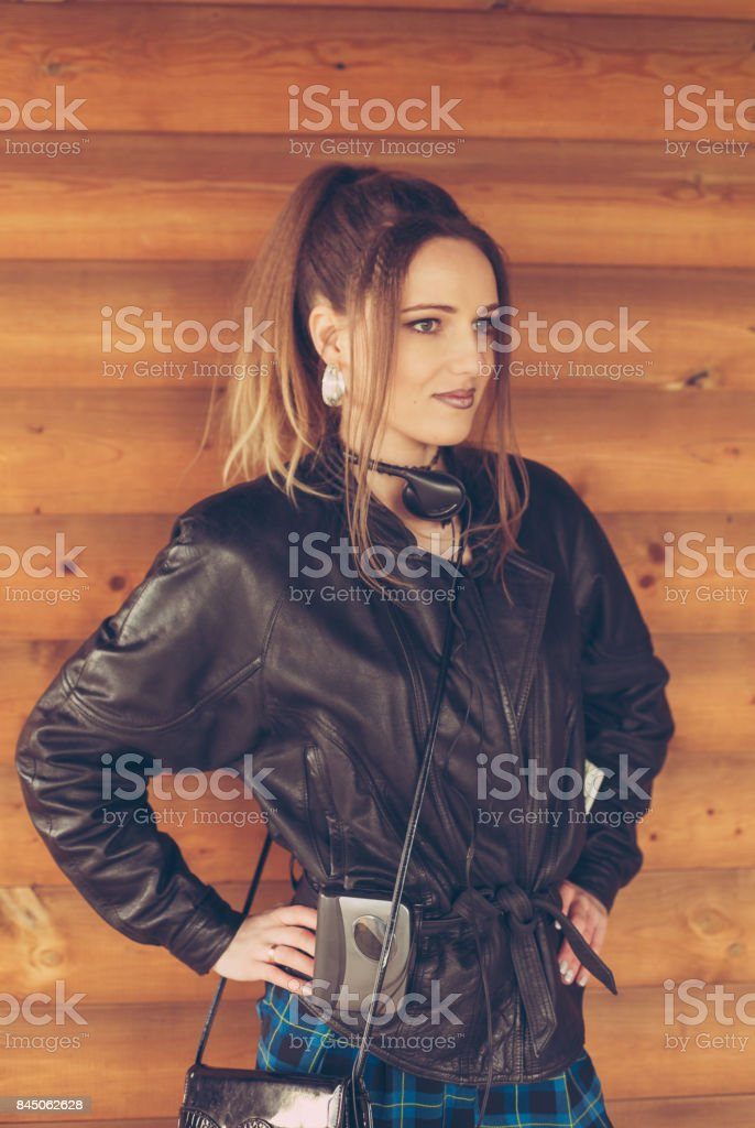 girl in clothes of the nineties, on the background of wooden wall stock photo