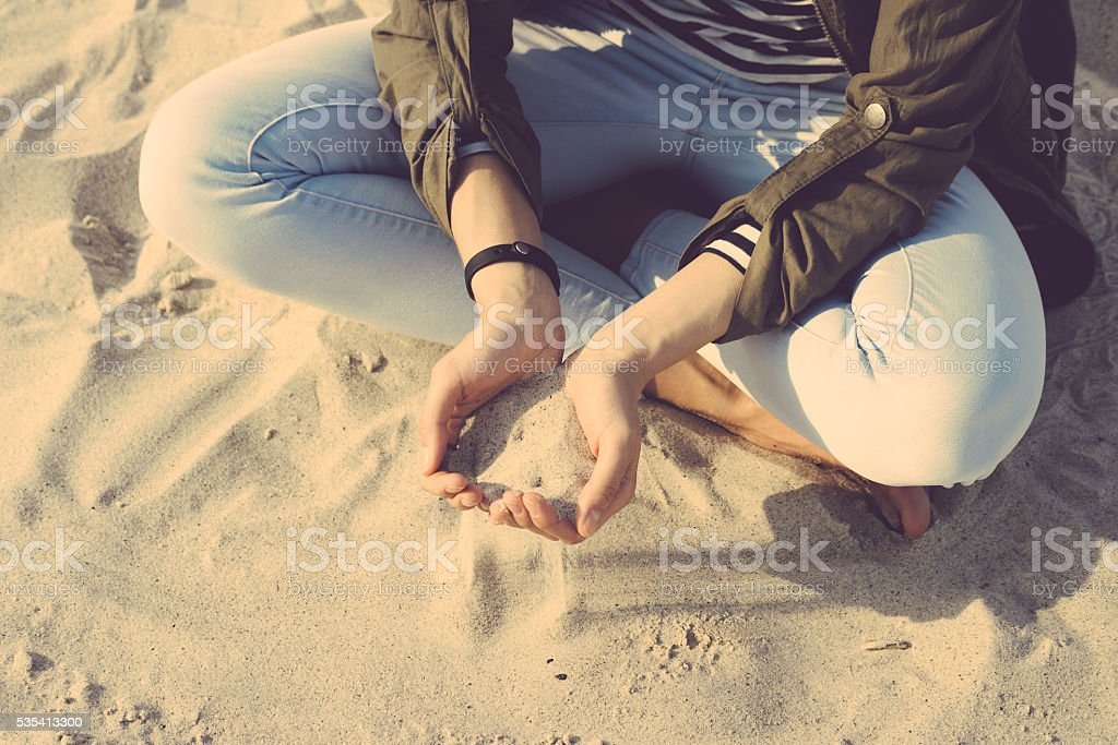 Girl in coat and jeans sitting on the beach cross-legged stock photo