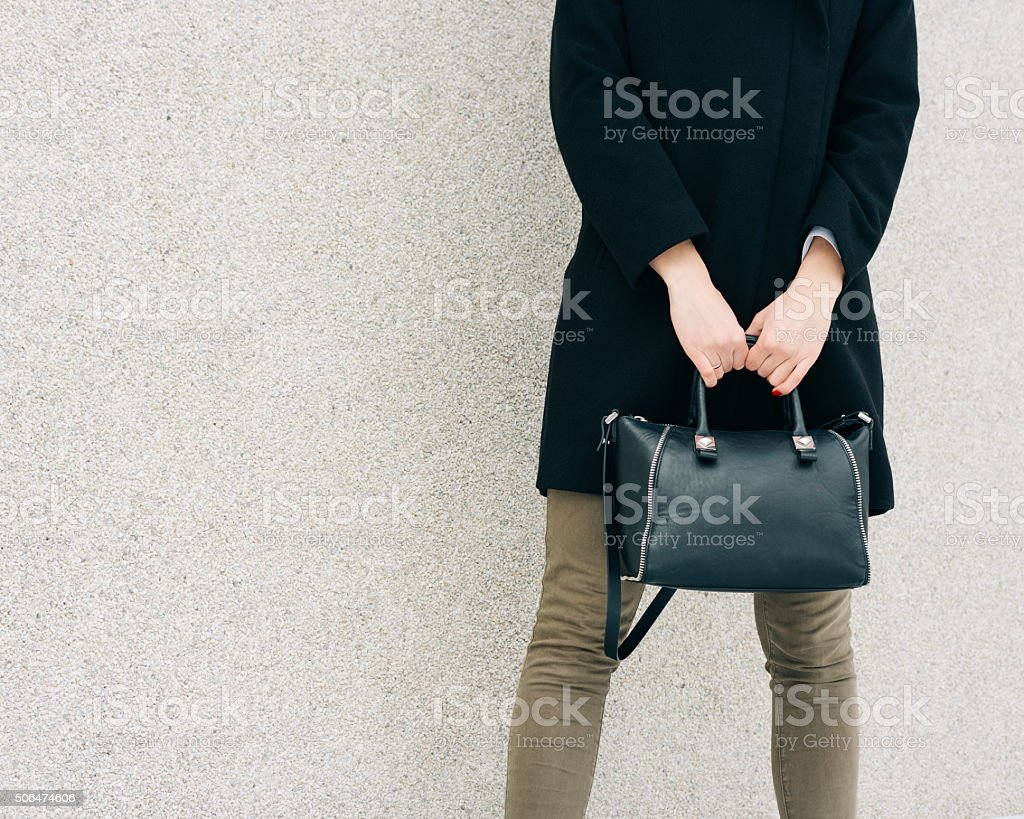 Girl in coat, jeans and a bag in her hand stock photo