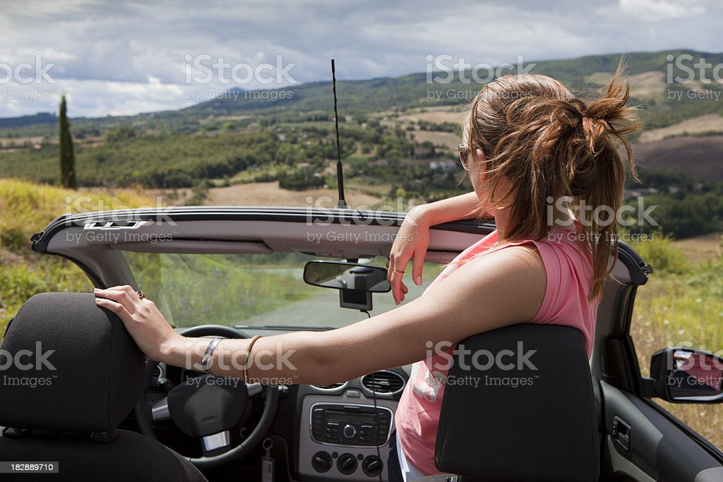Girl in convertable vehicle overlooking Tuscany landscape stock photo