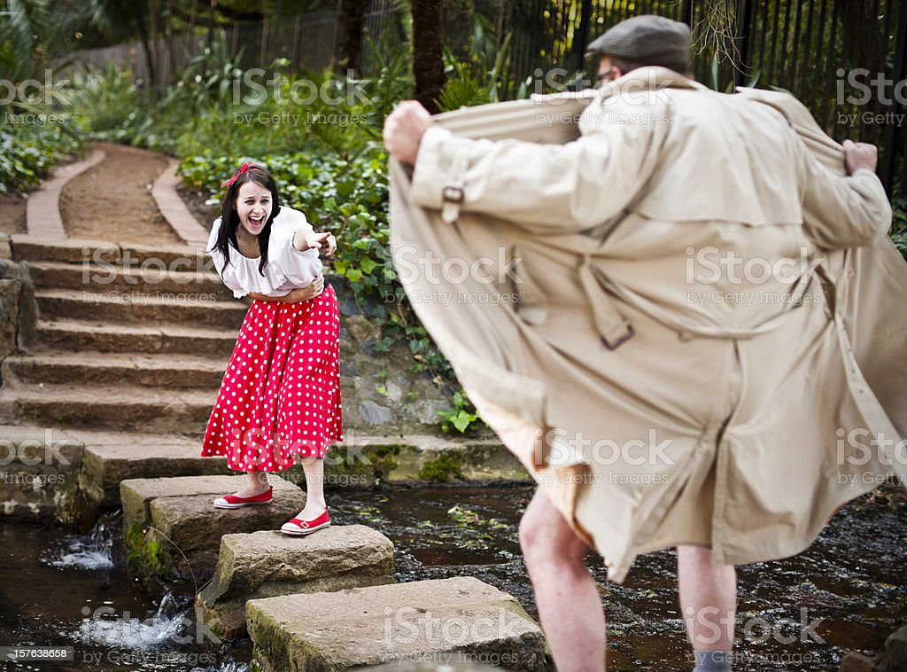 Girl in cute outfit laughs at raincoat clad flasher royalty-free stock photo