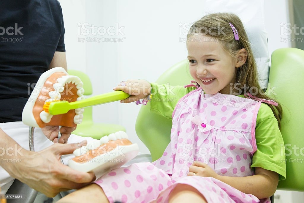 Girl in dentists chair toothbrushing a model stock photo