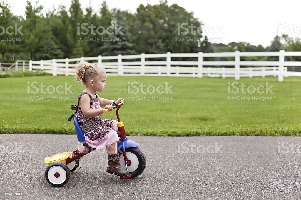 Girl in Dress & Cowboy Boots Riding Tricycle stock photo
