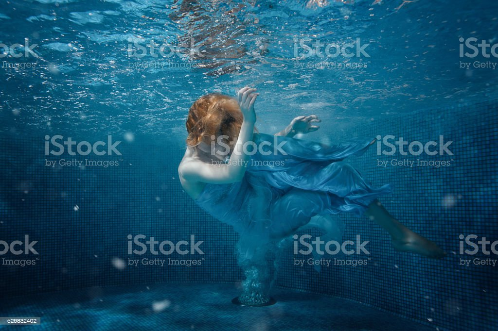 Girl in dress on bottom of the pool. stock photo