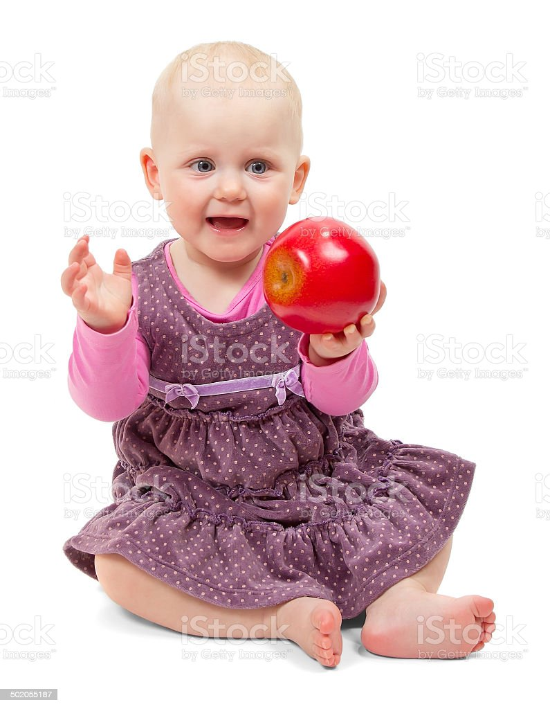 Girl in dress sits with an apple stock photo