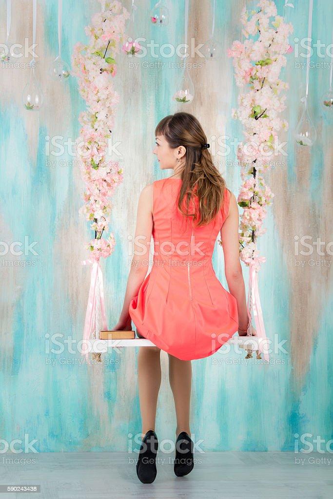 Girl in dress sitting on swing stock photo