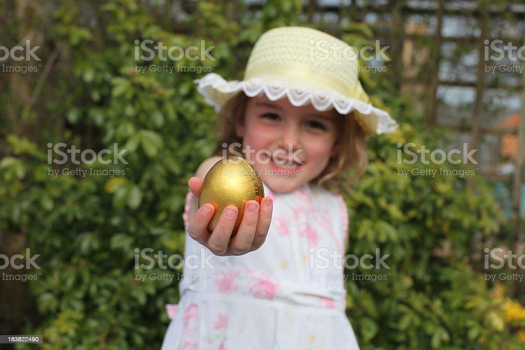Girl in easter bonnet and dress on egg hunt stock photo
