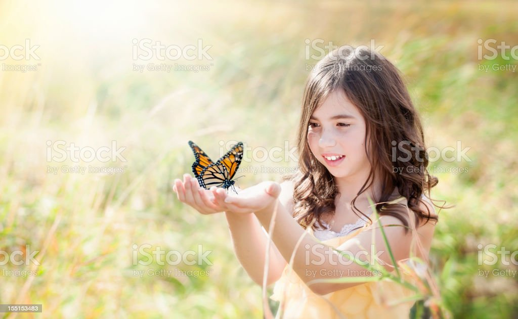 Girl in Field Holding a Monarch Butterfly royalty-free stock photo