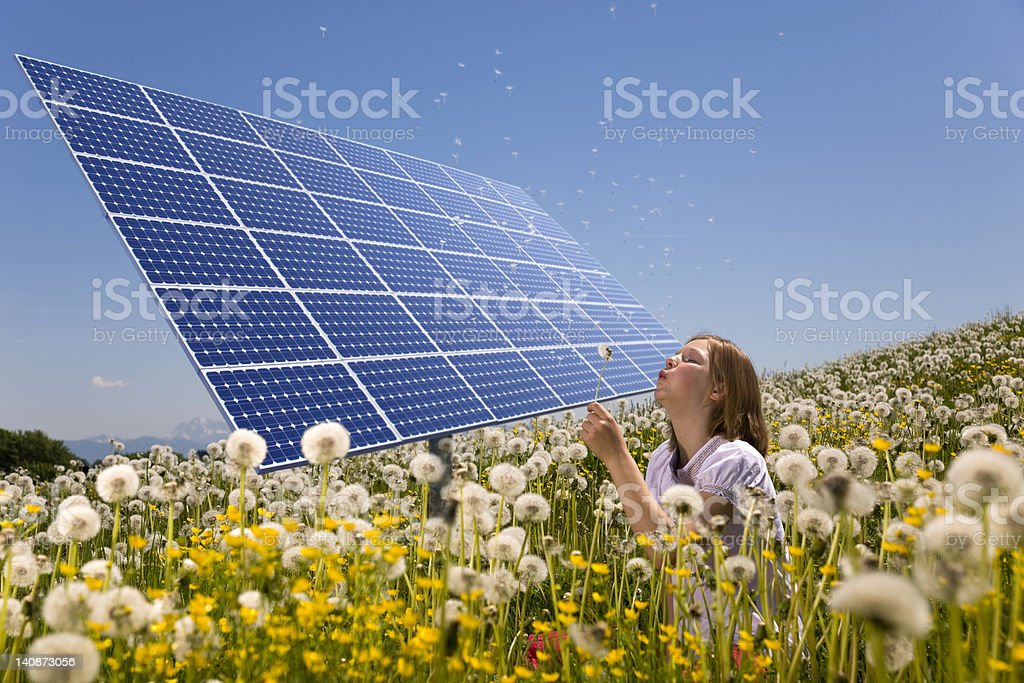 Girl in field with solar panels stock photo