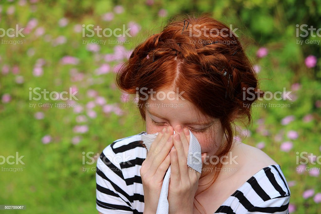 Girl in flower gardens with hayfever, blowing nose, sneezing, allergies stock photo