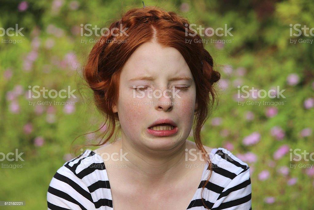 Girl in flower gardens with hayfever, sneezing, runny nose, allergies stock photo