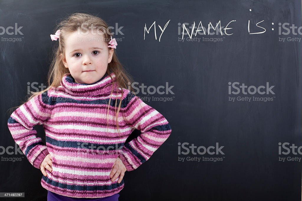 Girl in front of a chalkboard says my name is stock photo