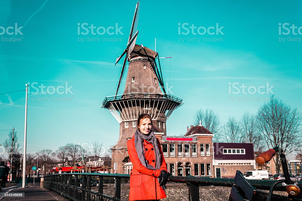 Girl in front of a windmill in Amsterdam, Netherlands stock photo