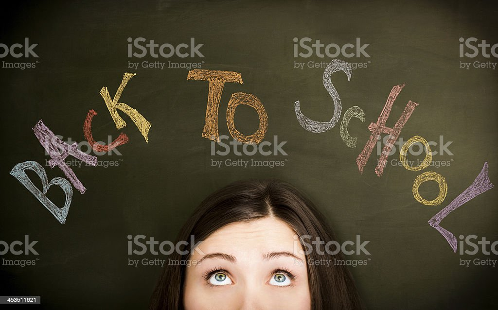 Girl in front of Back to school on blackboard. royalty-free stock photo