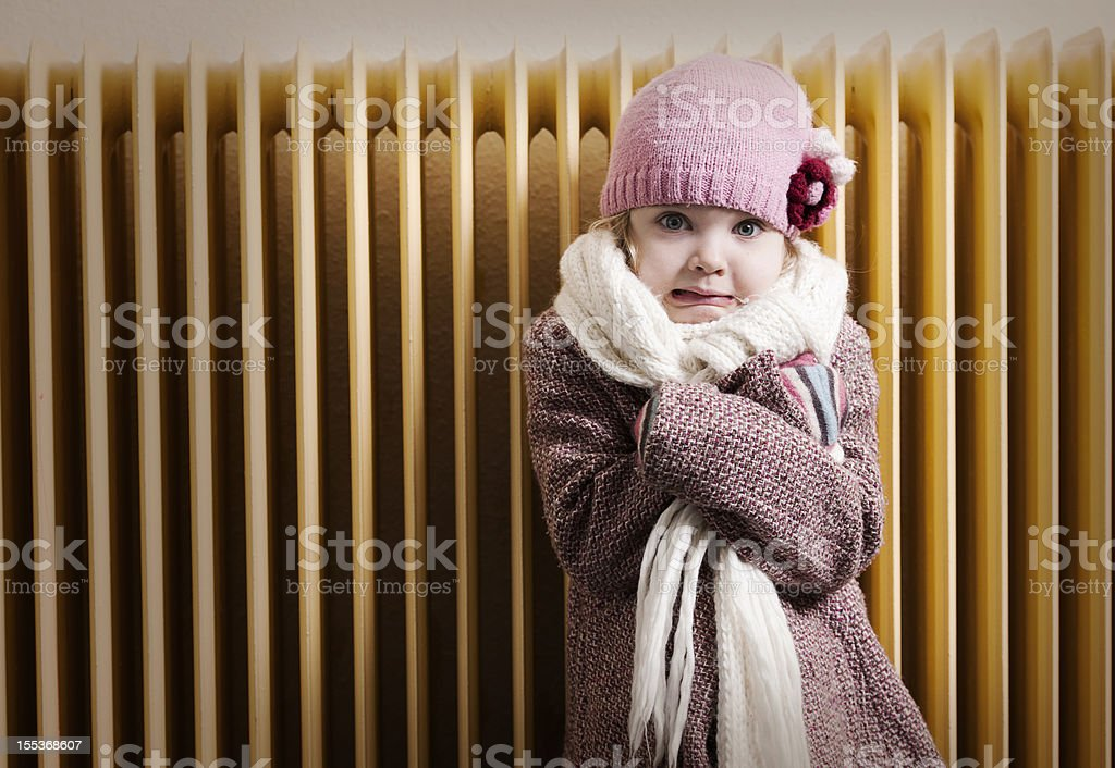 Girl in front of radiator stock photo
